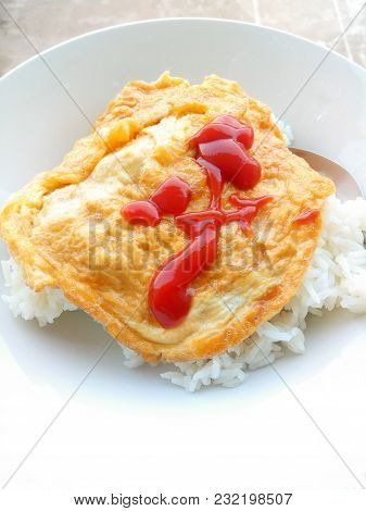 Omelet Rice Topped With Ketchup In White Plate. Thai Street Food