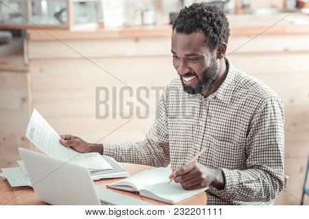 University Studies. Joyful Positive Nice Man Smiling And Reading His Lectures While Preparing The Ho