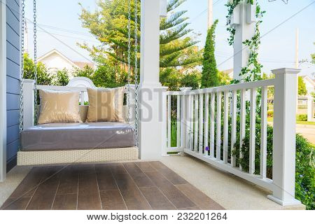 Brown Pillows On A Modern Swing At Balcony With Nature And Sky Background.