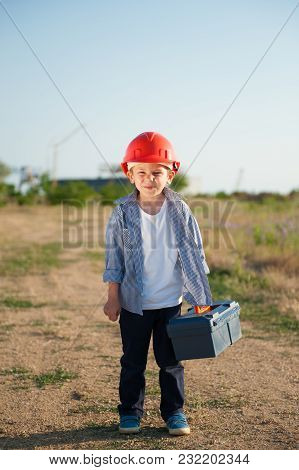 Funny Small Kid Wearing Orange Helmet With Box Of Tools Goes To Work