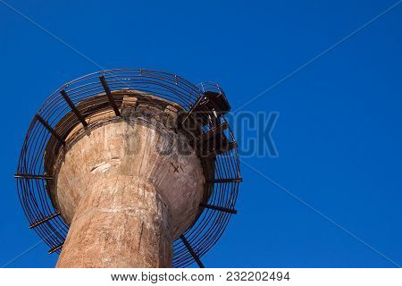 Industrial View From The Bottom Of Abandoned Lighthouse With Concrete Construction And Metal Element