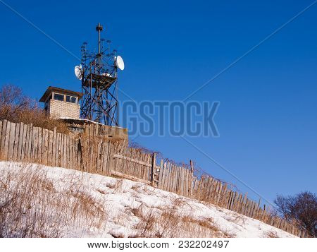 Winter View Of Old Military Base On Hill, Metal Tower With Radio-relay Antennas And Wooden  Fence Wi