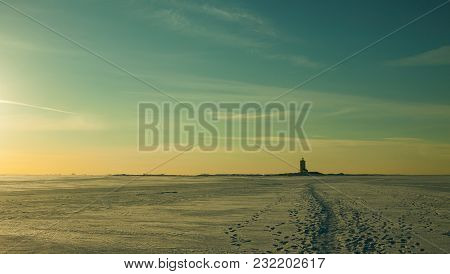Epic Winter Landscape With Blue Tones, Deserted Surface Of Frozen Sea Covered By Snow, Sunset Sky Wi