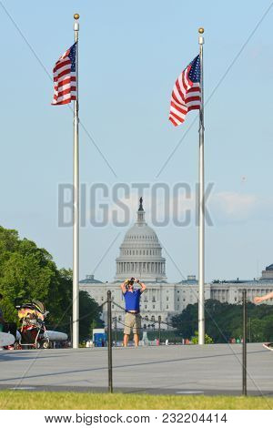 Washington DC / United States -01 June 2014: The people enjoy nice weather at Washington Monument grounds with a Capitol building background