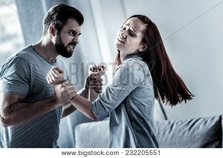 It Hurts Me. Exhausted Redhead Weak Woman Feeling Pain Standing Near Her Husband Who Holding Her Arm