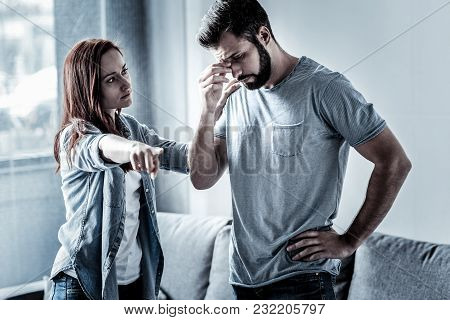 Get Out. Serious Calm Confident Woman Standing In The Bright Room Near Husband Looking At Him And Po