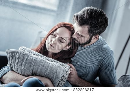 Forgive Me. Redhead Sad Exhausted Woman Hugging Pillows Sitting On The Sofa Near Her Husband Looking