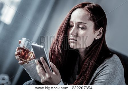 It Doesnt Matter. Upset Redhead Frustrated Woman Spending Time Alone In The Empty Room Holding A Gla