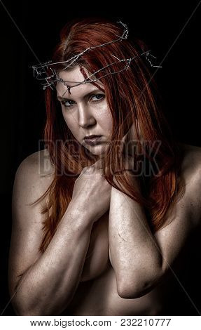 Sexy Beautiful Woman With A Wreath Of Barbed Wire On The Head On A Dark Background.