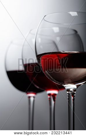 Glasses Of  Pink , Red And White Wine On A Dark Background.