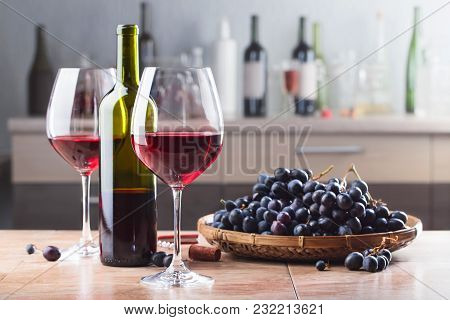Bottle And Glasses Of Red Wine With Grapes On A Kitchen Table.