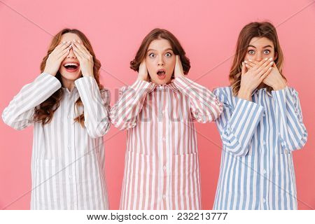 Three young women in home clothings showing symbols of tree wise monkeys - see no evil, hear no evil, speak no evil at sleepover isolated over pink background