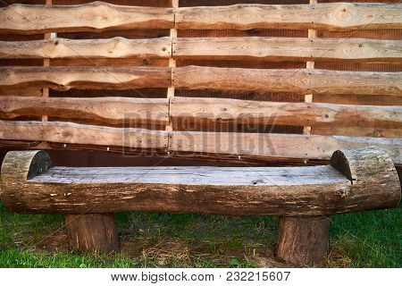 Wooden Rough Bench Against Wood Plank Wall Outdoor, Copy Space. Empty Wooden Bench Made Of Logs. Lon