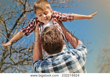 Just Fly. Low Angle Of A Positive Nice Boy In Hands Of His Loving Father Spinning Him Outdoors