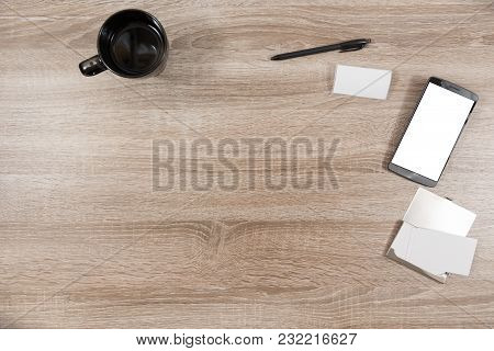 Top View On Wooden Desk With Smartphone With Empty Copy Space, Blank White Name Tag, A Black Pen, Bl