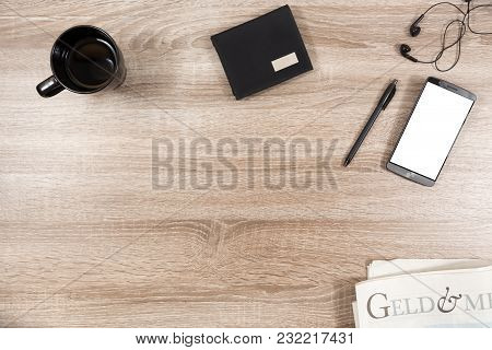 Top View On Wooden Desk With Smartphone With Empty Copy Space, Black Headphone Earpieces And Cables,