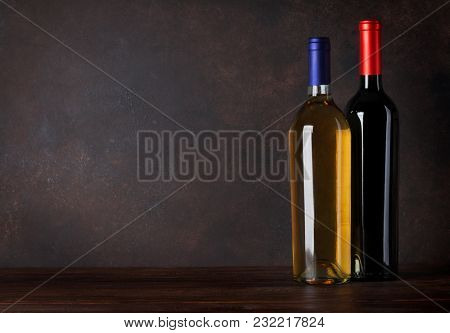 Red and white wine bottles in front of blackboard wall. With copy space for your text