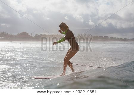 Silhouette Of Sportswoman Riding Wave On Surf Board In Ocean With Backlit