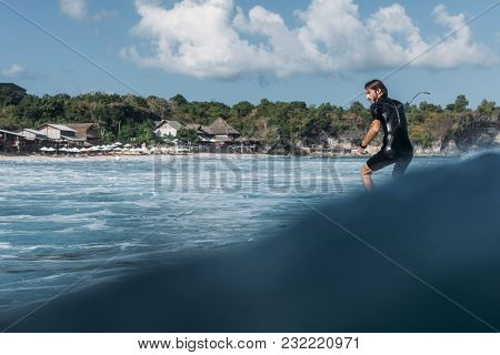 Man Riding Wave On Surf Board In Ocean
