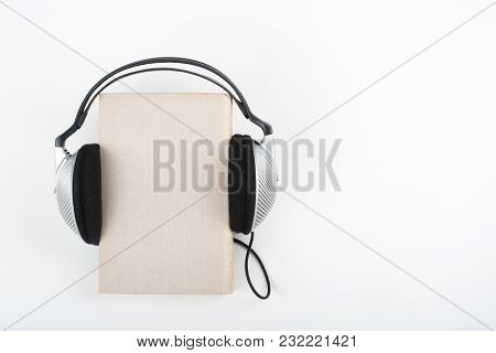 Audiobook On White Background. Headphones Put Book, Empty Cover, Copy Space For Ad Text. Distance Ed