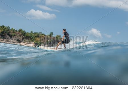 Active Man Surfing Wave On Surf Board In Ocean