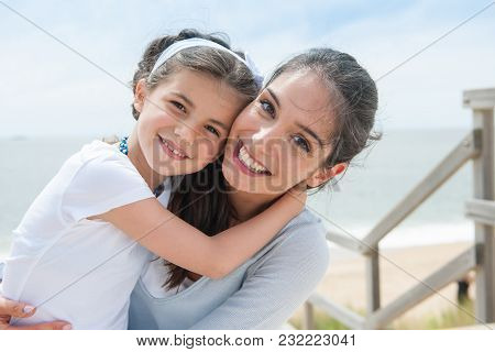 Beautiful Mom And Her Daugther At Seaside Smiling At Camera.