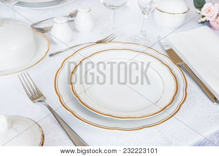 Beautifully Decorated Table With White Plates, Glasses, Cutlery And Flowers On Luxurious Tablecloths