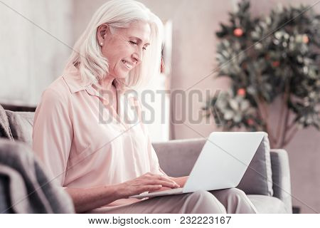 Have A Rest. Senior Cute Gray Haired Woman Sitting At Home Spending Time With Using The Laptop.