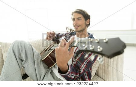 guy with guitar sitting on sofa in living room. concept of a lifestyle