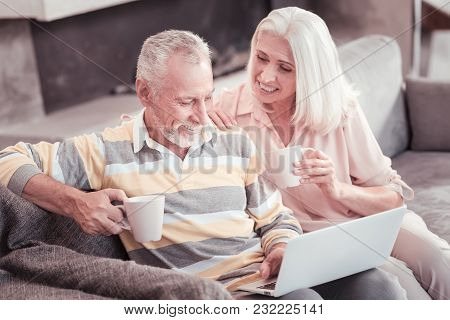 Have A Rest Together. Smart Joyful Senior Couple Sitting In The Bright Room On The Sofa Drinking Tea