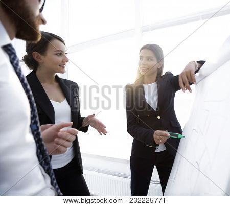 business woman pointing with a marker on the flipchart