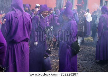 Antigua, Guatemala: March 18 2018: Two Young Purple Robed Men In Incense Smoke At The Procession Of