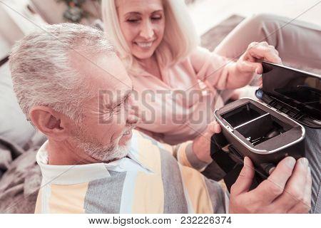 Its Not So Hard. Joyful Unshaken Aged Man Sitting On The Sofa Near His Wife Holding And Examining Th