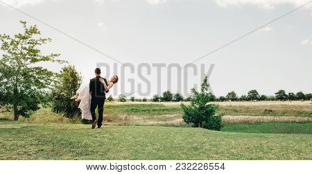 Groom Carrying The Bride At Park