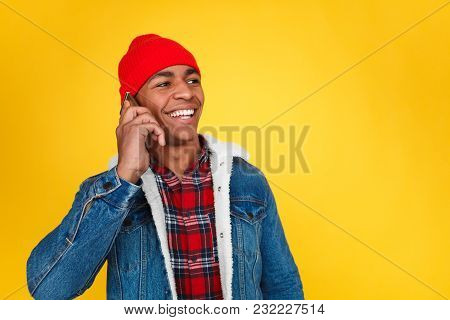 Stylish Ethnic Man In Denim Trendy Jacket And Red Hat Smiling While Speaking On Smartphone.