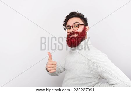 Handsome Guy In Glasses And With Beard In Red Glitters Holding Thumb Up Looking Confidently At Camer