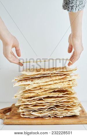 A Stack Of Plain Grilled Pita Bread On A Wooden Cutting Board With A White Background. Female Hands