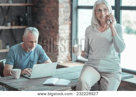 Im Listening. Pleasant Cute Senior Woman Sitting In The Room On The Table Near Her Husband Who Worki