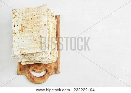 A Stack Of Plain Grilled Pita Bread On A Wooden Cutting Board With A White Background. Top View With