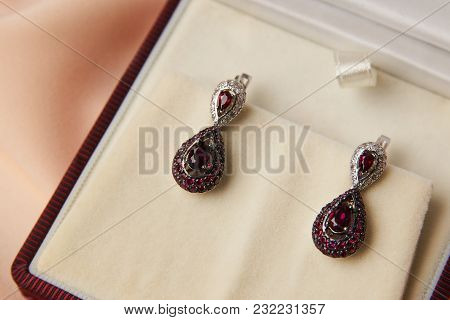 Pair Of Ruby Diamond Earrings With Red Ruby Stone On A Silk Peach Background. Luxury Female Jewelry