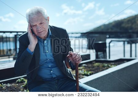 Chronic Headache. Tired Old Man Sitting Outdoors And Massaging His Temple While Suffering From A Sev
