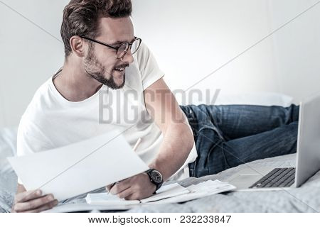 Working At Home. Cheerful Intelligent Handsome Man Holding Documents And Looking At The Laptop Scree