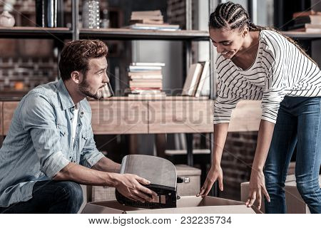 Where To Put It. Nice Young Positive Man Holding A Toaster And Looking At His Girlfriend While Packi