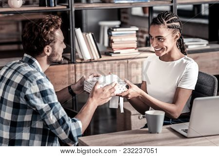 Birthday Gift. Cheerful Positive Nice Woman Smiling And Looking At Her Boyfriend While Receiving A G