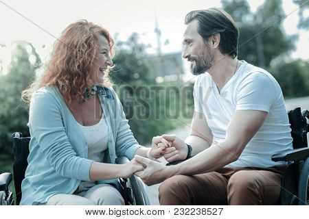 My Support. Cheerful Invalid Female Sitting On Her Wheelchair Near Her Man And Expressing Positivity