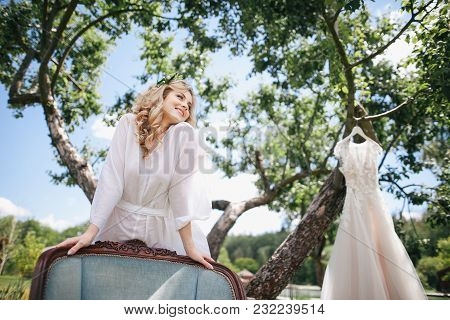 Low Angle View Of Happy Young Bride In White Robe Leaning At Chair While Wedding Dress Hanging On Tr