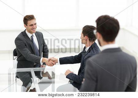 Businessmen making handshake in an office.