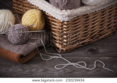 Knitting And Knitting Needles On A Wooden Surface