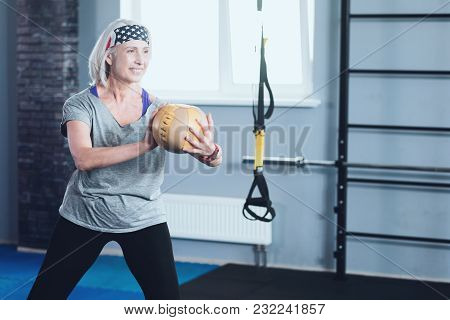 Enjoying My Retirement. Active Senior Lady Focusing On An Exercise While Standing In A Quarter Squat