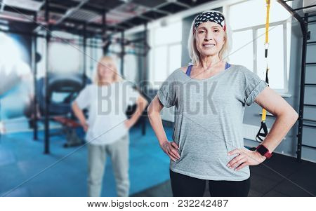 Get Up And Move. Hazel Eyed Elderly Lady Posing Into The Camera With Her Hands On The Hips While Sta